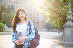 Muchacha del estudiante con los libros y la mochila que se colocan en sol encendido uni Foto de archivo libre de regalías