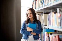 Muchacha del estudiante de la High School secundaria con el libro en la biblioteca Imagen de archivo