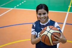 Muchacha del estudiante del adolescente con una bola de la cesta Imágenes de archivo libres de regalías