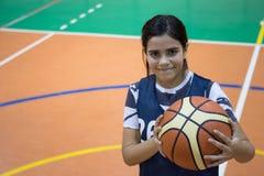 Muchacha del estudiante del adolescente con una bola de la cesta Fotografía de archivo libre de regalías
