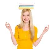 Muchacha del estudiante en actitud de la yoga con los libros en la pista Imagenes de archivo