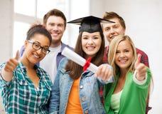 Muchacha del estudiante en casquillo de la graduación con el diploma Fotografía de archivo libre de regalías