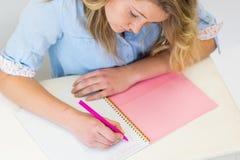 Muchacha del estudiante en el escritorio con el cuaderno y la escritura de la pluma Imagen de archivo