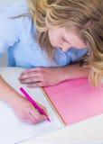 Muchacha del estudiante en el escritorio con el cuaderno y la escritura de la pluma Fotos de archivo