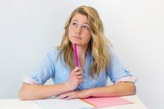 Muchacha del estudiante en el escritorio con el pensamiento del cuaderno y de la pluma Foto de archivo