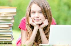Muchacha del estudiante en hierba con el ordenador portátil Imágenes de archivo libres de regalías