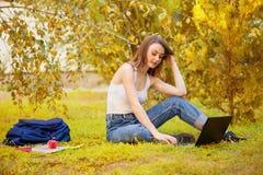 Muchacha del estudiante en hierba con un ordenador Fotografía de archivo libre de regalías