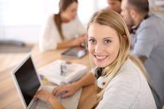 Muchacha del estudiante en la clase que trabaja en el ordenador portátil Imagenes de archivo