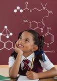 Muchacha del estudiante en la tabla que mira para arriba contra la pizarra roja con la escuela y el gráfico de la educación fotos de archivo libres de regalías