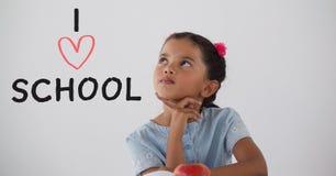 Muchacha del estudiante en la tabla que piensa contra el fondo blanco con el texto de escuela del amor de I fotos de archivo