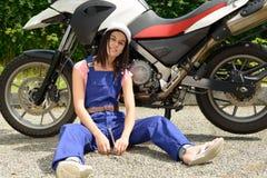 Muchacha del estudiante en mecánicos de la moto Imágenes de archivo libres de regalías