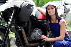 Muchacha del estudiante en mecánicos de la moto Foto de archivo libre de regalías