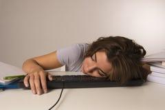 Muchacha del estudiante o trabajadora atractiva joven que se sienta en el escritorio del ordenador en dormir de la tensión cansad Fotos de archivo