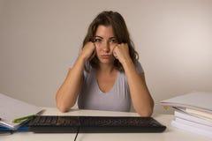 Muchacha del estudiante o trabajadora atractiva joven que se sienta en el escritorio del ordenador en la tensión que mira haber a Imagen de archivo libre de regalías