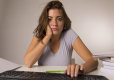 Muchacha del estudiante o trabajadora atractiva joven que se sienta en el escritorio del ordenador en la tensión que mira haber a Fotografía de archivo