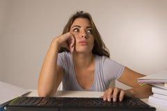 Muchacha del estudiante o trabajadora atractiva joven que se sienta en el escritorio del ordenador en la tensión que mira haber a Imagenes de archivo