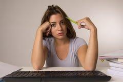 Muchacha del estudiante o trabajadora atractiva joven que se sienta en el escritorio del ordenador en la tensión que mira haber a Fotos de archivo libres de regalías