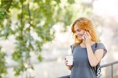 Muchacha del estudiante que camina con café en un fondo del parque concepto de la juventud Copie el espacio Imagen de archivo