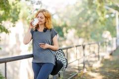 Muchacha del estudiante que camina con café en un fondo del parque concepto de la juventud Copie el espacio Foto de archivo