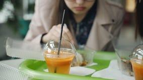 Muchacha del estudiante que come en tallarines chinos de un café durante una rotura Taza del primer con el jugo de zanahoria rec almacen de metraje de vídeo