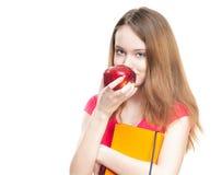 Muchacha del estudiante que come la manzana. Fotos de archivo libres de regalías