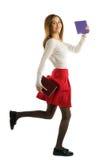 Muchacha del estudiante que corre con los cuadernos aislados en el fondo blanco Imagen de archivo