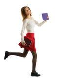 Muchacha del estudiante que corre con los cuadernos aislados en el fondo blanco Fotos de archivo