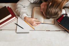 Muchacha del estudiante que duerme en el escritorio con endecha del plano de los libros Imagen de archivo libre de regalías