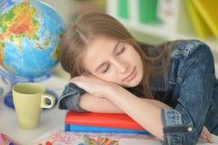 Muchacha del estudiante que duerme en los libros Fotografía de archivo libre de regalías