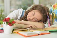 Muchacha del estudiante que duerme en los libros Fotos de archivo libres de regalías