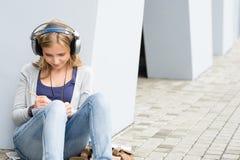 Muchacha del estudiante que escribe y que escucha la música Imágenes de archivo libres de regalías