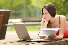 Muchacha del estudiante que estudia con un ordenador portátil en un campus universitario Imagen de archivo libre de regalías