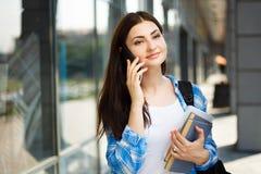 Muchacha del estudiante que habla en el teléfono móvil que coloca estructura cercana de la universidad Fotografía de archivo