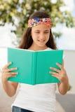 Muchacha del estudiante que lee un libro al aire libre Imagenes de archivo