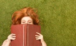 Muchacha del estudiante que miente con el cuaderno Imagen de archivo libre de regalías