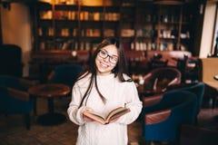 Muchacha del estudiante que ríe y que sostiene un libro en biblioteca Imágenes de archivo libres de regalías