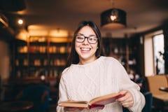 Muchacha del estudiante que ríe y que sostiene un libro en biblioteca Imagen de archivo libre de regalías