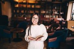 Muchacha del estudiante que ríe y que sostiene un libro en biblioteca Fotos de archivo libres de regalías