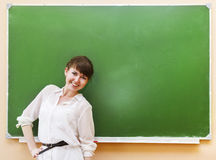 Muchacha del estudiante que se coloca cerca de la pizarra limpia en la sala de clase Fotos de archivo libres de regalías