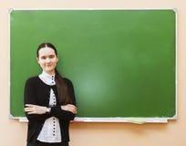 Muchacha del estudiante que se coloca cerca de la pizarra limpia en la sala de clase Foto de archivo