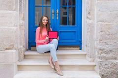 Muchacha del estudiante que se sienta con una tableta delante de puertas azules Imagen de archivo
