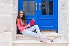 Muchacha del estudiante que se sienta con una tableta delante de puertas azules Fotografía de archivo libre de regalías