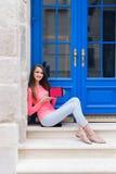 Muchacha del estudiante que se sienta con una tableta delante de puertas azules Imagenes de archivo