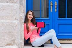 Muchacha del estudiante que se sienta con una tableta delante de puertas azules Foto de archivo libre de regalías