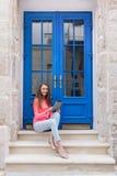 Muchacha del estudiante que se sienta con una tableta delante de puertas azules Fotos de archivo