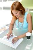 Muchacha del estudiante que se sienta detrás del ordenador portátil moderno del escritorio Fotos de archivo libres de regalías
