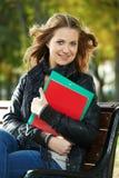 Muchacha del estudiante que se sienta en banco al aire libre Fotos de archivo