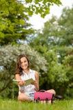 Muchacha del estudiante que se sienta en el libro de lectura de la hierba Imagenes de archivo