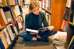 Muchacha del estudiante que se sienta en el piso y que lee un libro en la biblioteca Foto de archivo libre de regalías