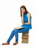 Muchacha del estudiante que se sienta en la pila de libros Imagen de archivo libre de regalías